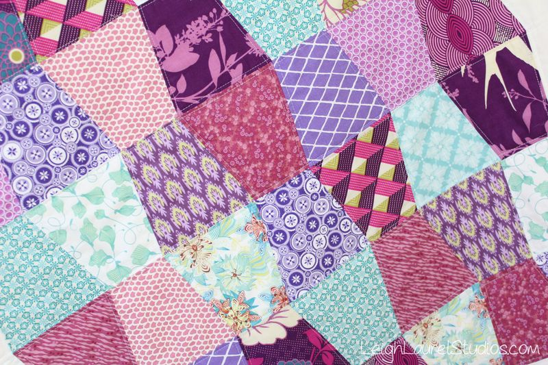 Closeup of scrappy baby tumbler quilt by karin jordan