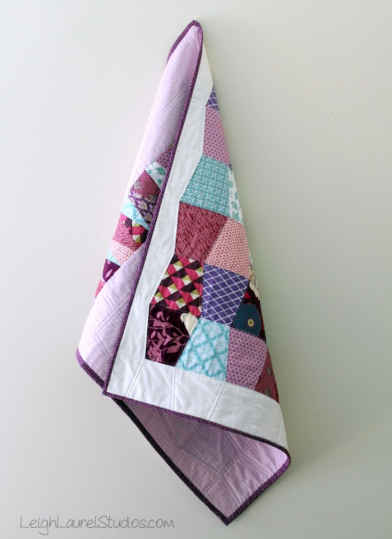 Scrappy baby tumbler quilt in pinks, purples and teal by karin jordan
